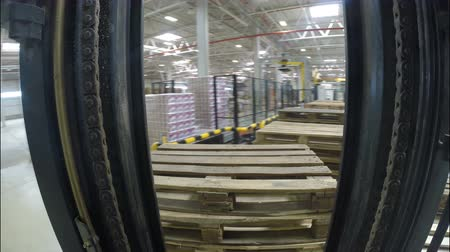 yükleyici : KAZAN, TATARSTAN  RUSSIA - JUNE August 2015: Camera moves with two vertical devices loader carries wooden pallet set across big light spacious warehouse on June 08 in Kazan
