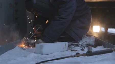 welding helmet : man in welding helmet and protective clothes welds snow-covered machine components in Arctic at night Stock Footage