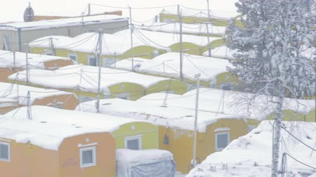 ubytování : snowy town of yellow prefabricated lodges for construction workers and watchmen amidst trees in Yamal in Russia