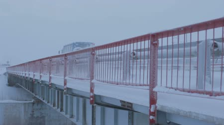 ограждение : big truck moves fast on new snowy bridge with red metal guardrail above Arctic circle in Russia