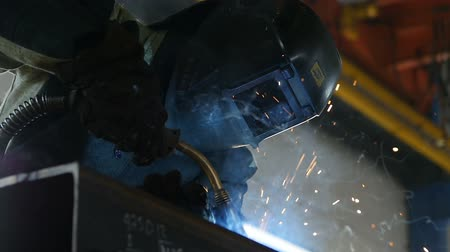 fire facilities : KAZAN, TATARSTAN  RUSSIA - DECEMBER 20 2016: Slow motion closeup professional welder finishes welding and takes off protective mask in plant workshop on December 20 in KAZAN Stock Footage