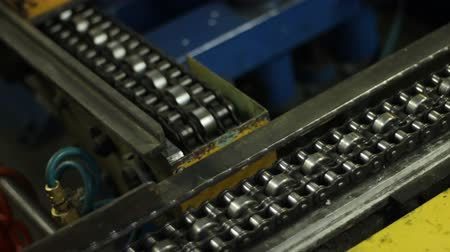 dik : closeup metal conveyor belts move with different speed perpendicular each other in production plant workshop