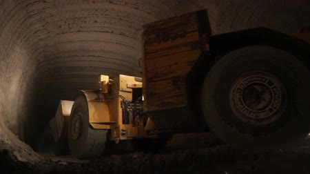 pedreira : powerful huge heavy mining machinery moves carefully inside dark narrow tunnel in limestone mine