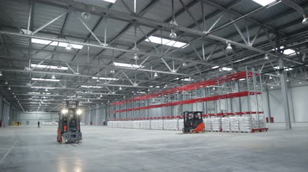 yükleyici : cargo machine moves in enormous spacious capacious large light warehouse with big loaded boxes Stok Video