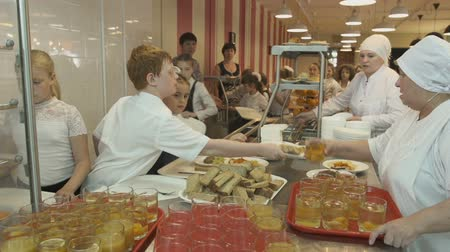 levou : KAZAN, TATARSTAN  RUSSIA - JANUARY 20 2017: Wideshot chef in white uniform at distribution of food in school cafeteria hold out glass of drink to schoolgirl on January 20 in Kazan Vídeos