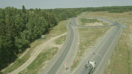 avançar : air plan camera move along the two country road with LED lamp where ride truck with tank and car Stock Footage
