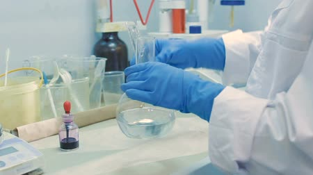 flasks : lab assistant in blue rubber gloves and white lab coat mixes reagents in flask in brightly lit laboratory Stock Footage