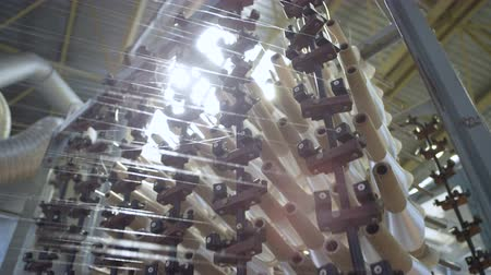 machine sous : panorama of operating spinning shop with lots of turning white thread bobbins at bright light