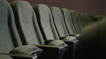 samet : closeup camera move along one row of empty gray soft chair in dark cinema hall