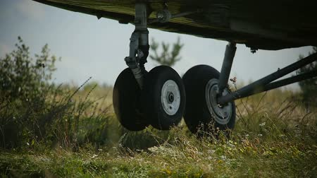 machine sous : closeup camera shows large helicopter landing gear wheels landing on meadow wind shakes grass against blue sky Stock Footage