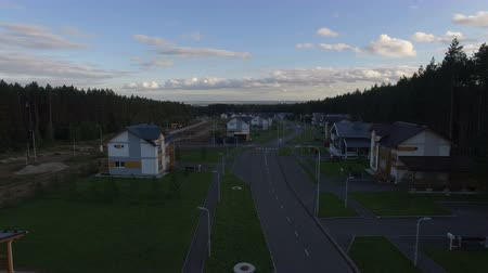 toward : upper view camera moves toward horizon leaving streets with neat cottages and surrounding forest at sunset