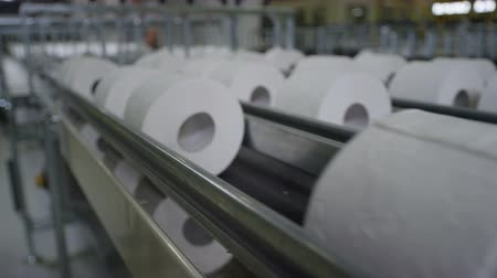 toilet paper : close view of long conveyor with toilet paper moving slowly in large light factory workshop Stock Footage