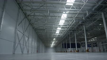 distribution lectrique : slow motion camera moves left inside big gray high empty factory room storage with bright lights on ceiling Stock Footage