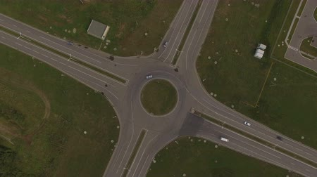 crossway : aerial view small cars move on asphalt crossroad around green circle