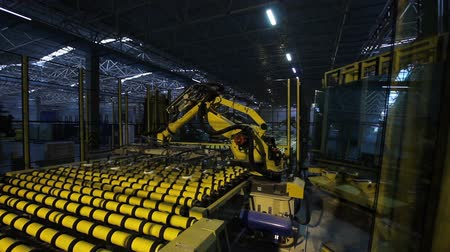 emme : huge yellow machine robot moves large glass sheet uses suction cups in modern glass production plant workshop in Alabuga