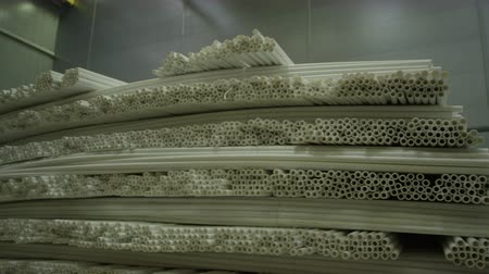 gyártó : camera moves slowly along large long shelves of produced white thin polyethylene pipes in factory storehouse