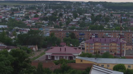perspective : panoramic view big city with beautiful white houses under neat red roofs trees against clear evening sky