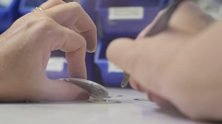 solder : closeup woman with manicure brazes round metal perforated details with soldering iron on white surface at workplace Stock Footage