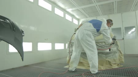 machine sous : painter in white boiler suit paints car bumper by sprayer in painting box Stock Footage
