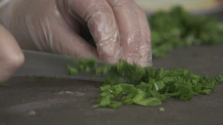 кинза : closeup macro cook hands cut cilantro on wooden board by professional knife