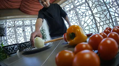 pepř : cook in uniform comes to table with vegetables red tomatoes pepper takes onion starts cutting on board in kitchen