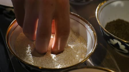 pasztet : closeup cook hand touches flour by fingers in bowl on kitchen table against bright daylight