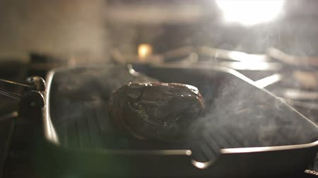глыба : closeup large meat lump grills in pan on stove open flame in steam clouds in bright light background in kitchen