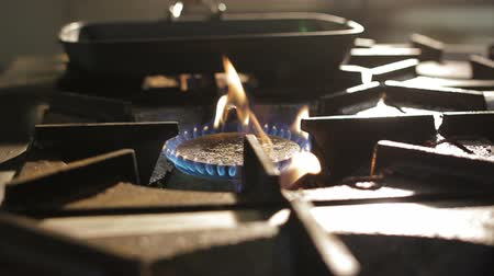 kitchenware : close view burner open flame of gas stove against black pan under bright light in kitchen