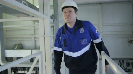 distribution lectrique : KAZAN TATARSTAN  RUSSIA - DECEMBER 20 2016: Professional worker in protective white helmet walks on bridge and inspects equipment in plant workshop on December 20 in Kazan