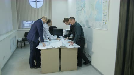 reseach : KAZAN, TATARSTAN  RUSSIA - DECEMBER 20 2016: Camera moves fast to people looking at data graphics on a table in a small room with a map on wall on December 20 in Kazan Stock Footage