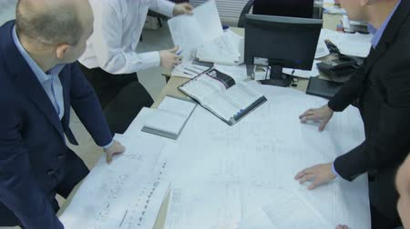 reseach : KAZAN, TATARSTAN  RUSSIA - DECEMBER 20 2016: Upper view business people looking at new data graphics on table in small room with map on wall on December 20 in Kazan