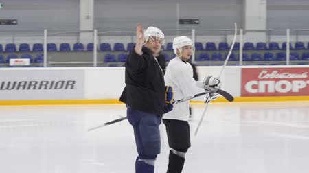 připomínka : KAZAN, TATARSTAN  RUSSIA - SEPTEMBER 12 2016: Slow motion people move on ice and trainer tells remarks to hockey player beginner at training on September 12 in Kazan