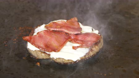 almôndega : closeup delicious meat cutlet with cheese and bacon fried on black metal surface in modern kitchen Vídeos