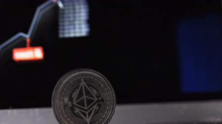 stabil : closeup camera moves from stabile growing to black ethereum coin model on foreground