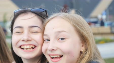 льдом : KAZAN, TATARSTAN  RUSSIA - SEPTEMBER 07 2017: Fast motion closeup happy laughing girls with ice-creams hug and pose in camera during rest on September 07 in Kazan