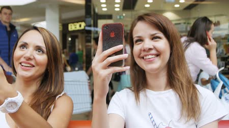 hall : KAZAN, TATARSTAN  RUSSIA - SEPTEMBER 19 2017: Happy smiling stylish women sitting on red sofa and take kids photo on smartphones in shopping mall on September 19 in Kazan