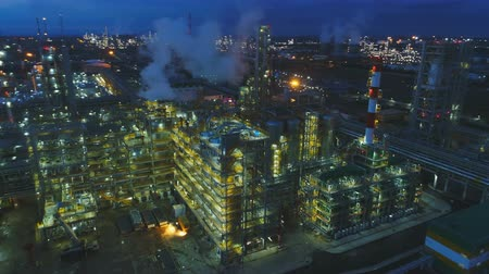 petroleum refinery : drone rotates above high buildings with blinking light in darkness