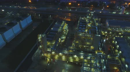 petroleum refinery : drone flies over refinery territory with illuminated buildings covered steam coming out of pipes