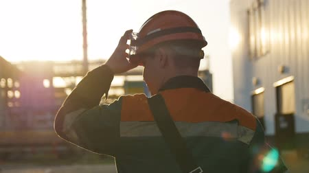 metal worker : slow motion backside view skilled worker in outfit walks along huge refinery territory under sunshine Stock Footage