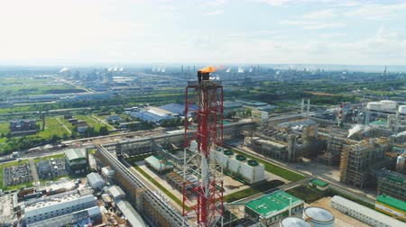 rurociąg : aerial view white and red torch tower above refinery territory with storage tanks and workshops Wideo