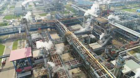 petroleum refinery : flycam rotates and shows huge gas and oil refinery plant with pipelines workshops and towers in white smoke Stock Footage