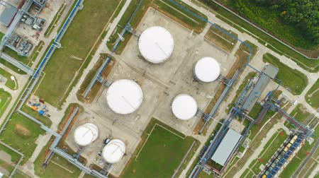 pipelines : flycam approach large oil tanks located on heavy industry plant territory with green lawns Stock Footage
