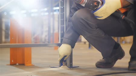distribution lectrique : slow motion worker in gloves and orange vest puts metal fastening in hole in metal construction