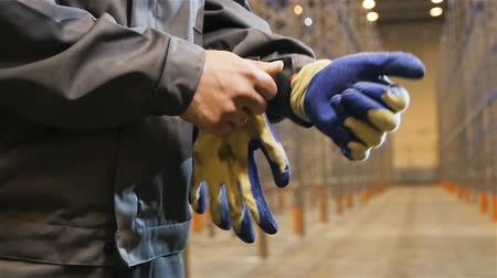 distribution lectrique : slow motion closeup skilled worker in uniform stands on blue-white gloves against large metal racks in warehouse