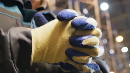 distribution lectrique : slow motion closeup worker in blue and white gloves claps his hands against flow focus metal racks in warehouse Stock Footage