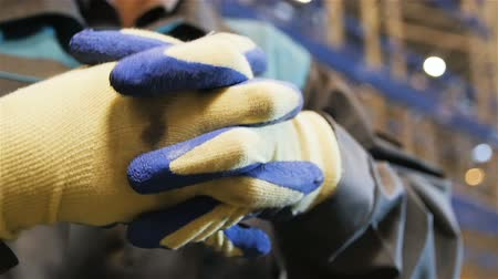 distribution lectrique : slow motion closeup person in gray uniform and blue-white working gloves in a large warehouse Stock Footage