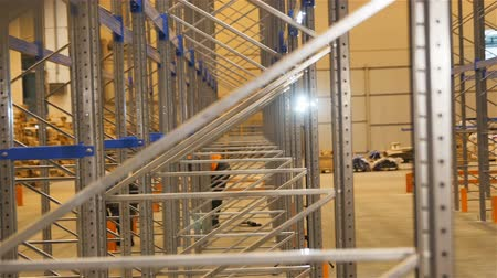 distribution lectrique : camera moves along large modern shining metal racks and workers in orange vests in background