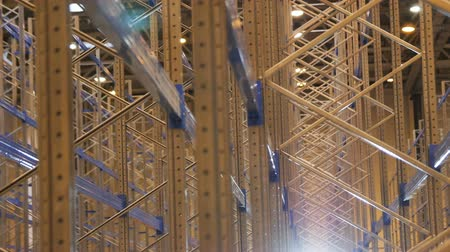 completo : camera shows large modern shining metal rack construction against bright light in empty warehouse Stock Footage