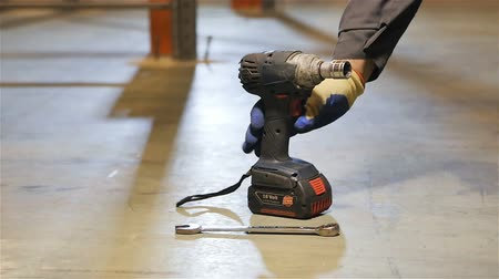 distribution lectrique : slow motion closeup person in working gloves takes black drill tool from concrete floor in a large warehouse Stock Footage