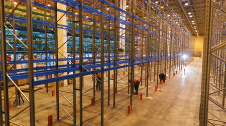 distribution lectrique : motion up above large warehouse with assembled modern metal racks and skilled workers at construction
